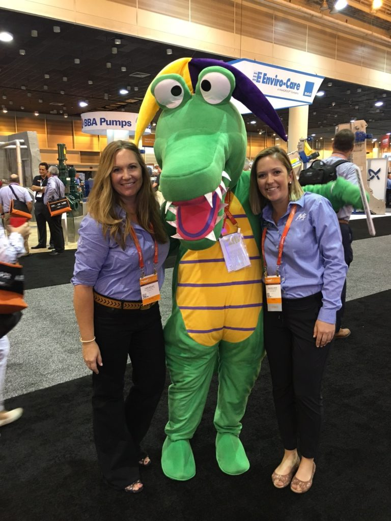 Nelson Schmidt employees posing with another organization's mascot at a trade show